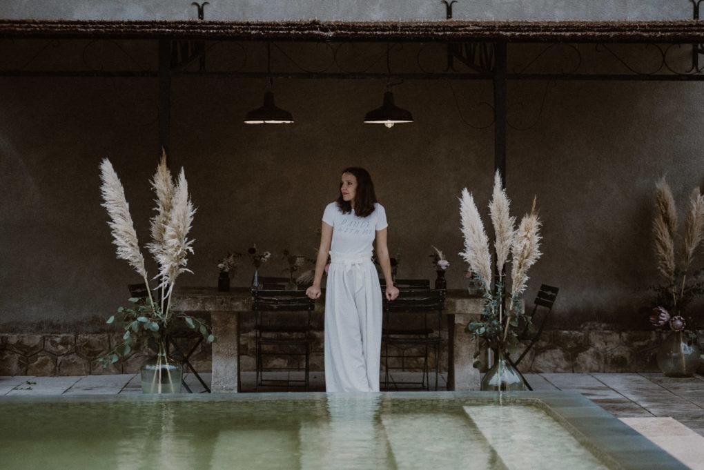 Plan d'ensemble du pantalon Emio, plan d'eau au premier plan et table aux fleurs en arrière plan