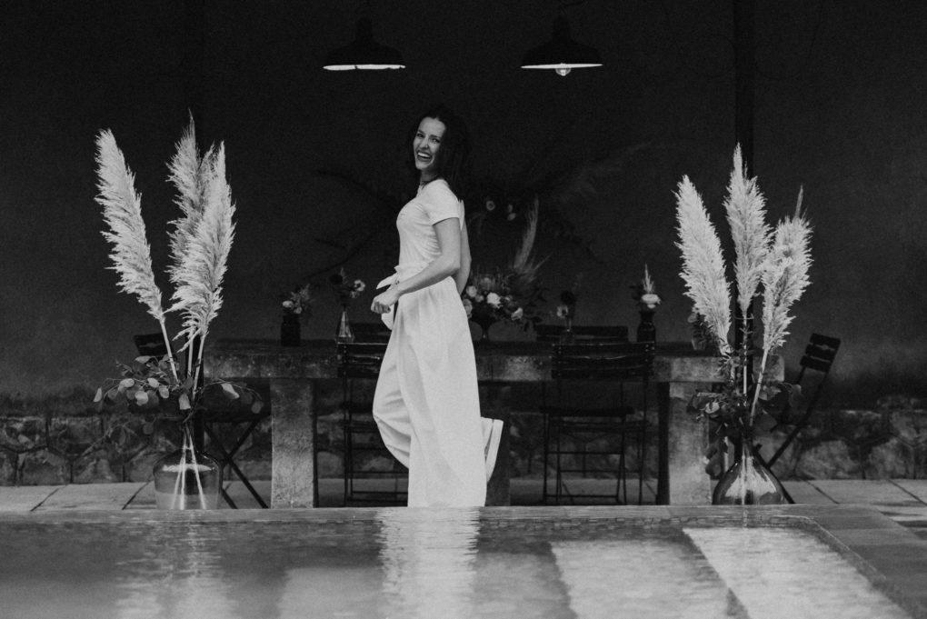 Photo en noir et blanc, plan d'ensemble du pantalon Emio devant la table aux fleurs