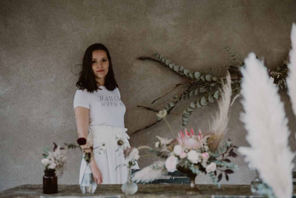 Photo du pantalon Emio avec des bouquets de fleurs autour, posés sur une table