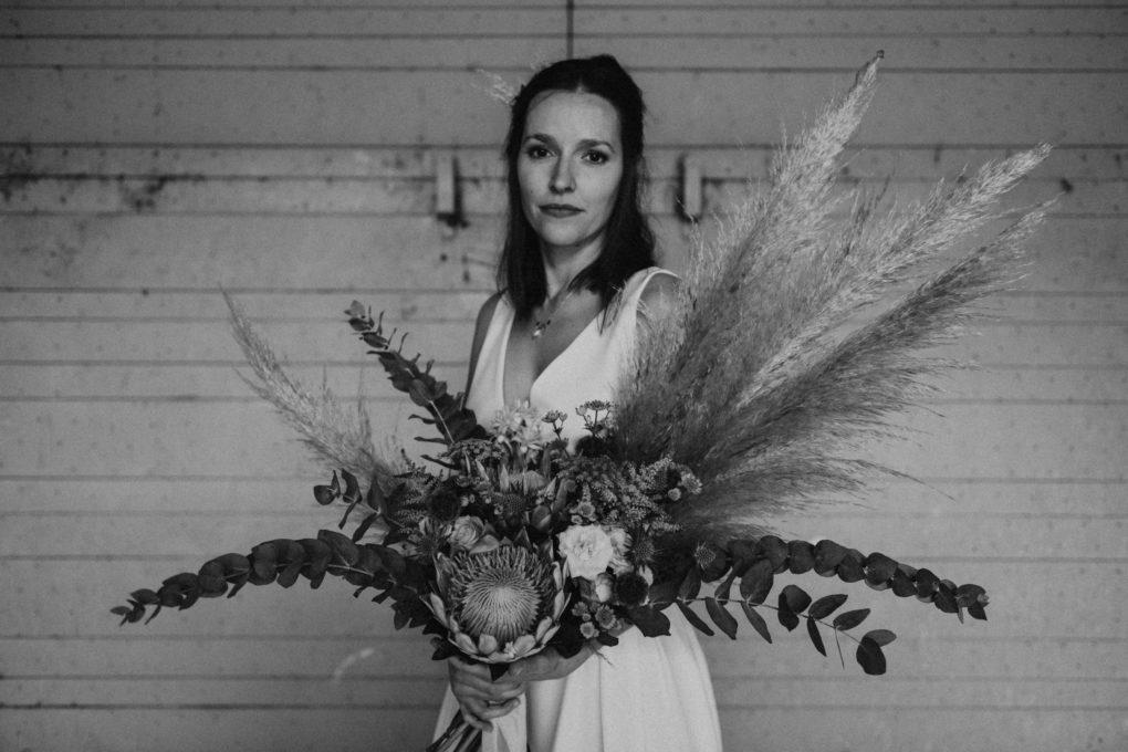Photo en noir et blanc, plan taille, de la robe Irene portée avec un bouquet de fleurs séchées