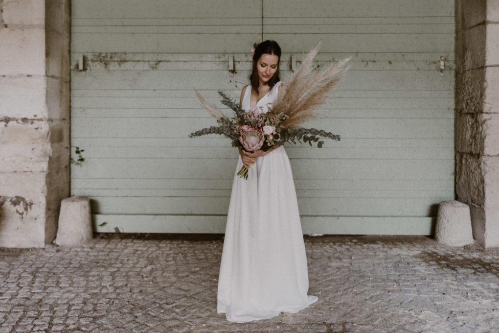 Plan large de la robe Irene portée avec un bouquet de fleurs séchées