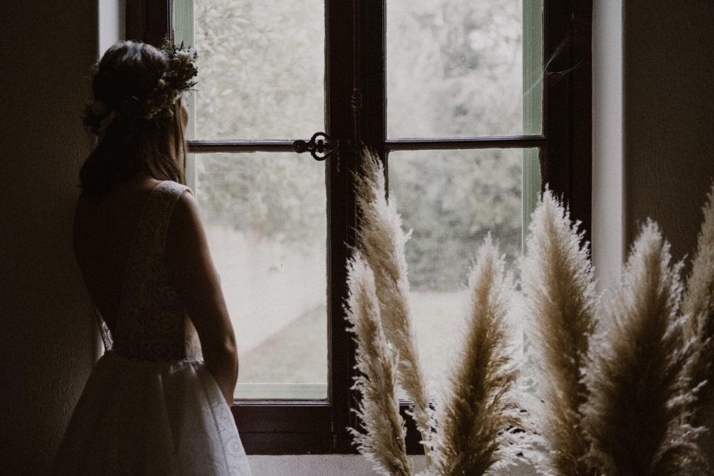 Plan d'ensemble de la robe Sasha portée, devant une fenêtre