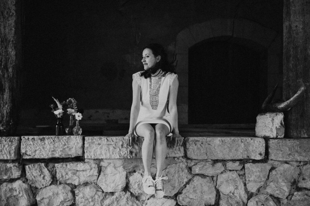 Photo de la robe Edwige en noir et blanc, portée par une femme assise sur un mur en pierre