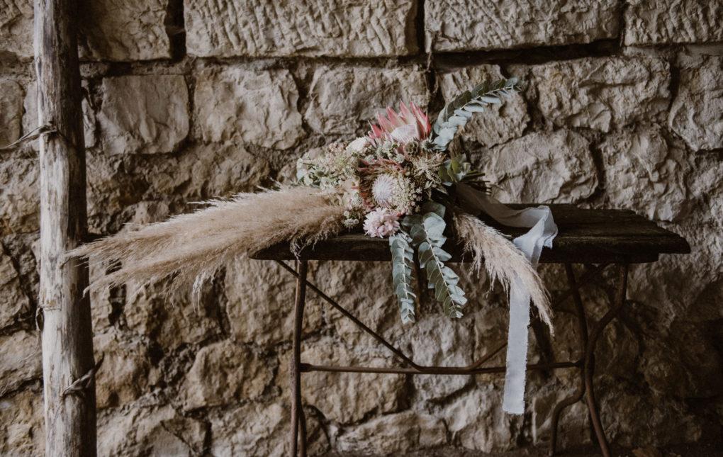 Photo du bouquet de fleurs séchées sur une table, devant un mur en pierre