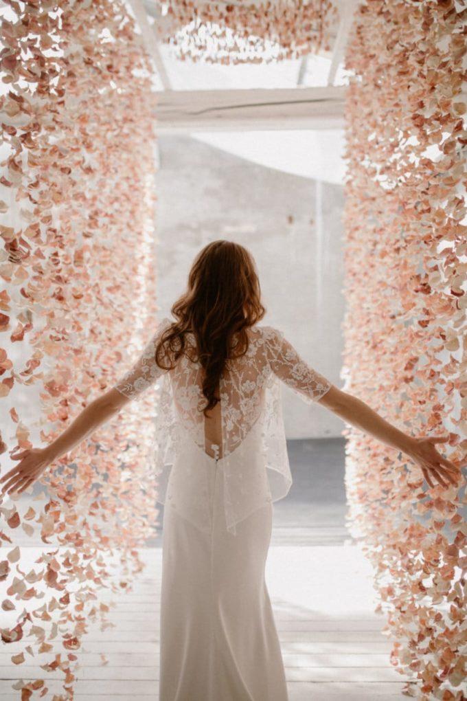 Photo de la robe Ares entre les rideaux de fleurs, détails dans le dos