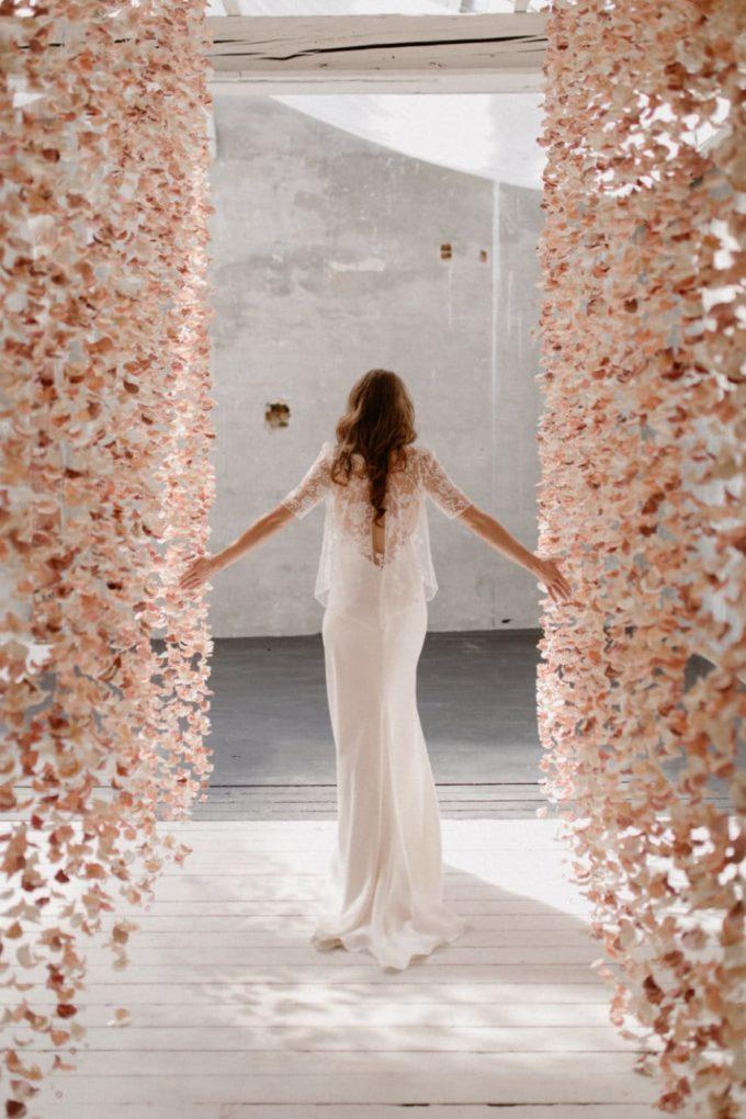 Plan large de la robe Ares de dos entre les rideaux de fleurs