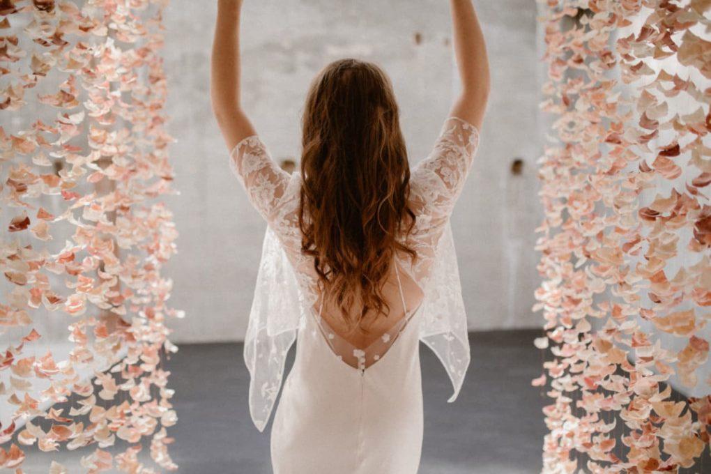 Plan rapproché du dos de la robe Ares entre deux rideaux de fleurs