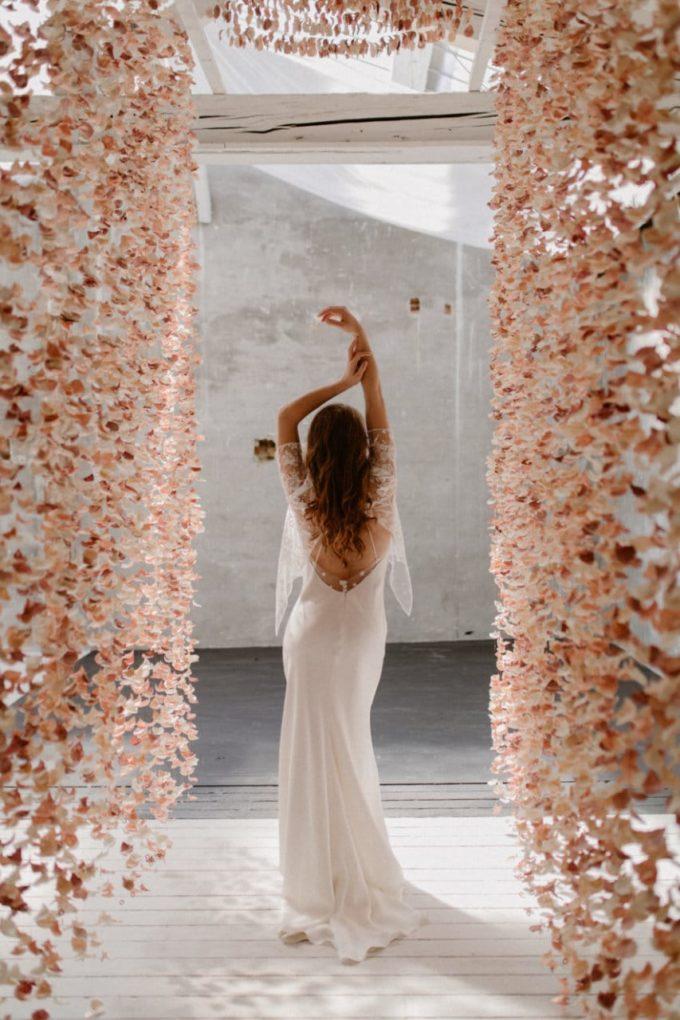 Photo de plein pied de la robe Ares de dos entre deux rideaux de fleurs