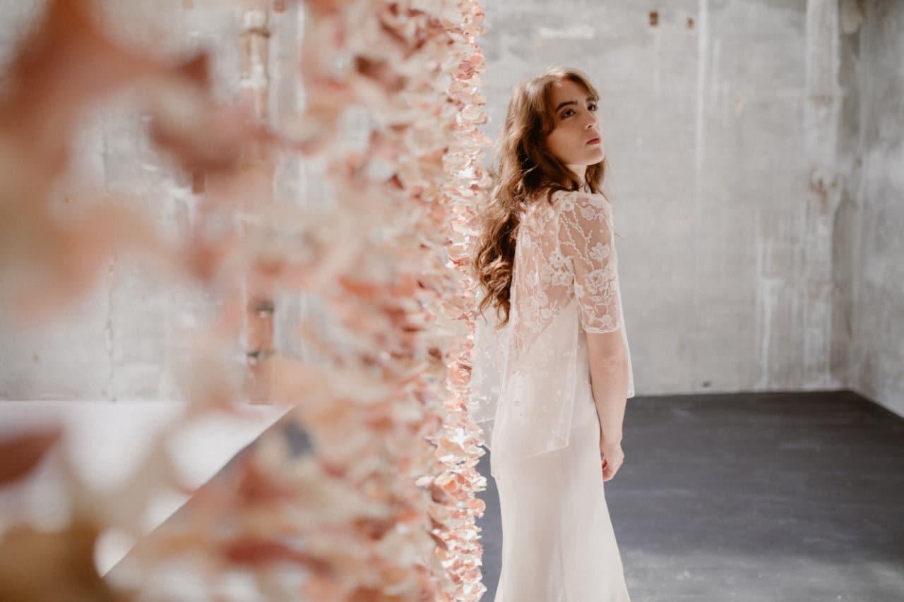 Photo de la robe Ares de profil devant le rideau de fleurs