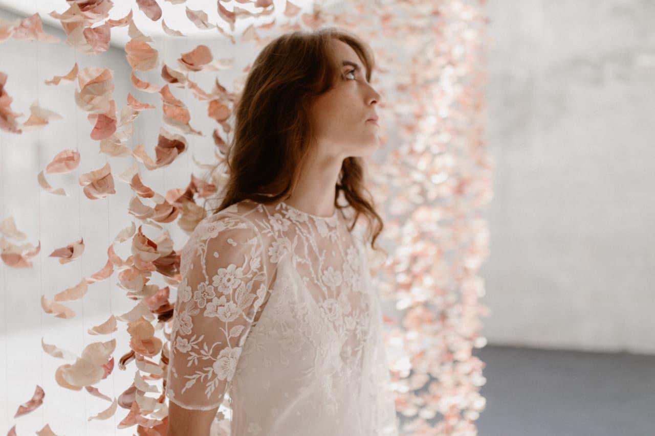 Plan 3/4 du haut de la robe Ares devant le rideau de fleurs