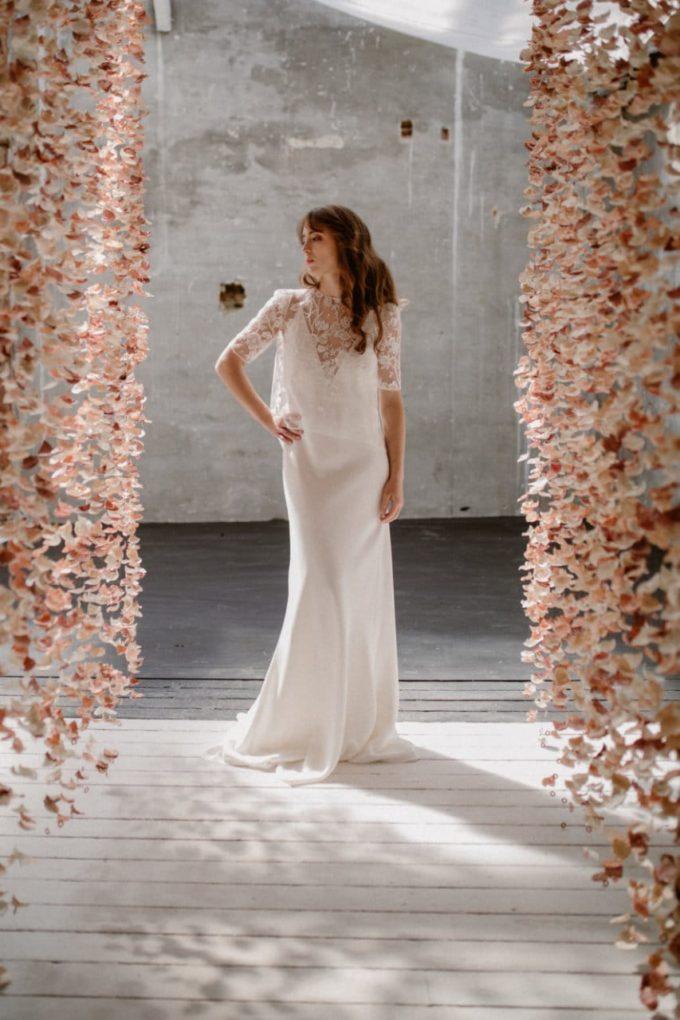 Photo de la robe Ares de face entre les rideaux de fleurs
