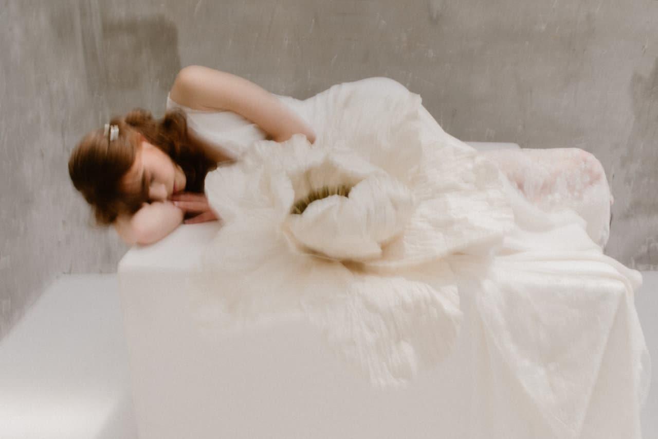 Photo en flou artistique de la robe Axelle portée par une femme allongée