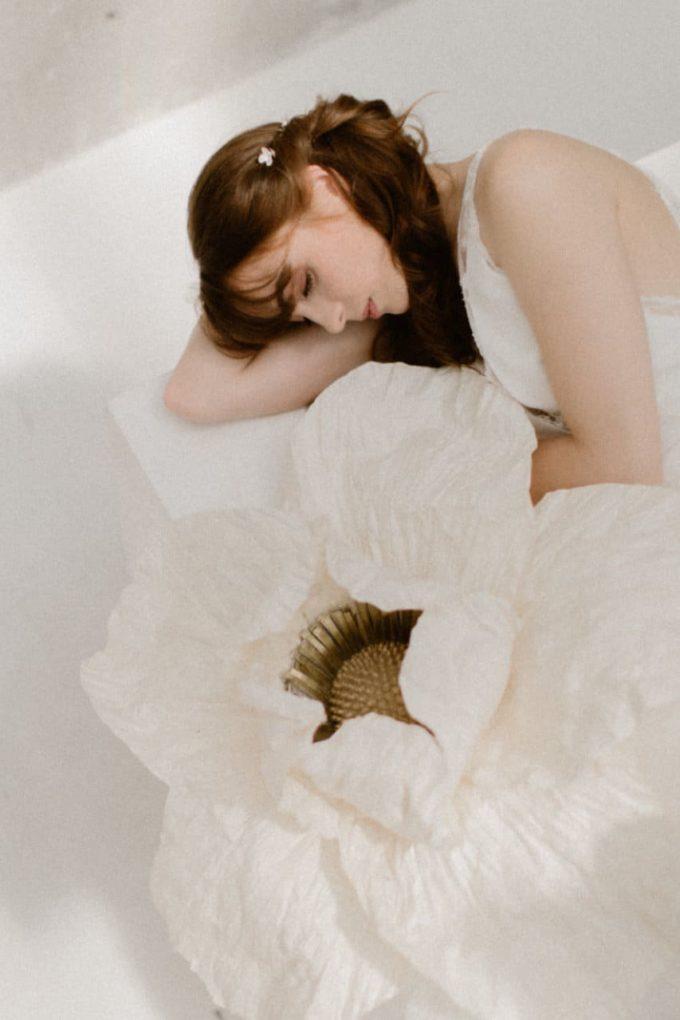 Photo de la robe Axelle portée par une femme allongée à côté d'une fleur, plan centré sur le haut