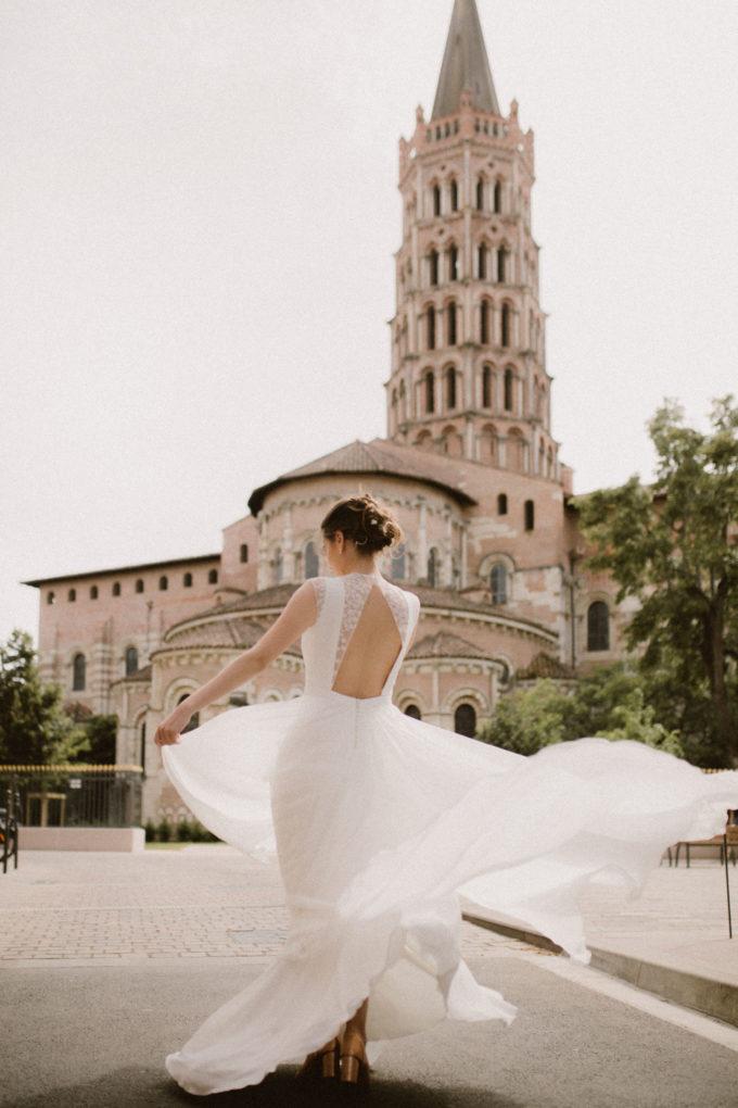 Photo de dos, plein pied, de la robe de mariée Hannah devant la Basilique Saint Sernin à Toulouse