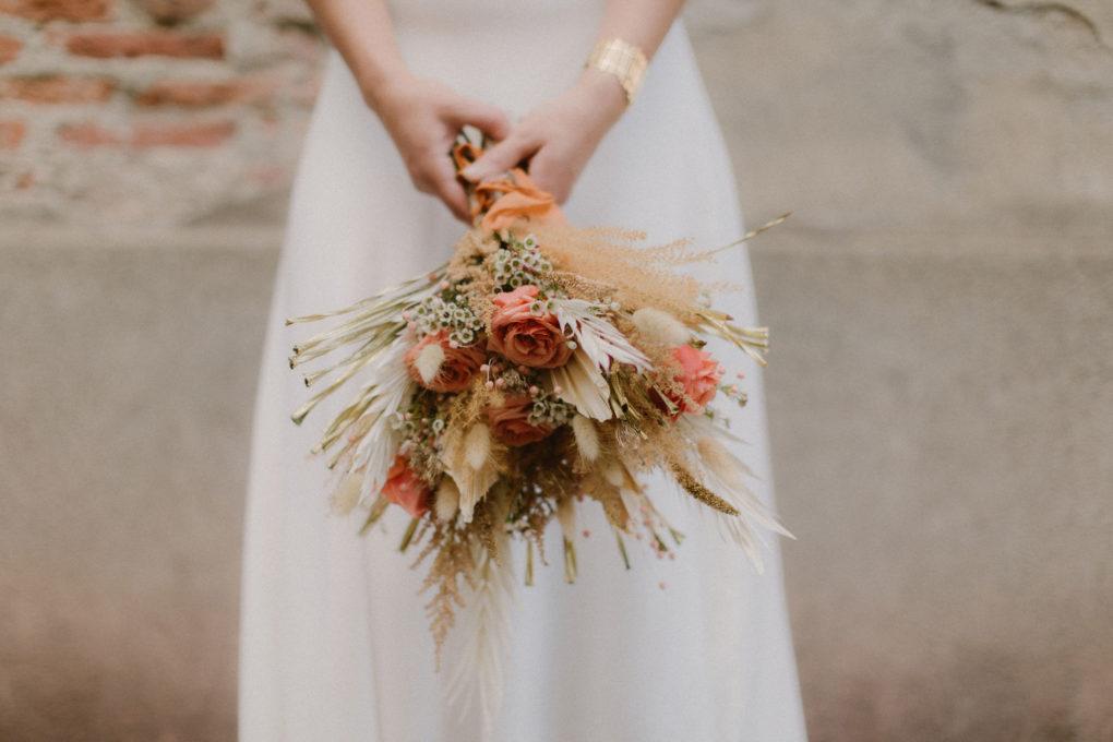 Gros plan sur le bouquet de La Baraque à Fleurs avec la robe Ida en arrière plan