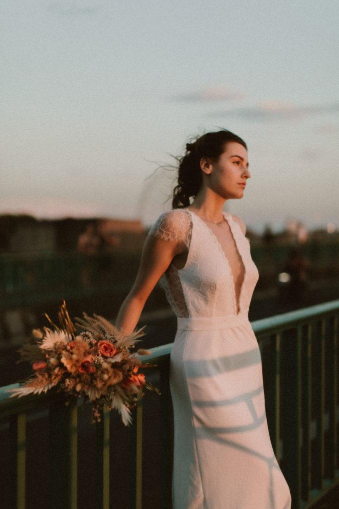 Photo de la robe June portée sur un pont au coucher de soleil