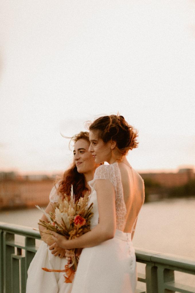 Plan taille des robes June et Allister portées par des femmes qui posent sur un pont