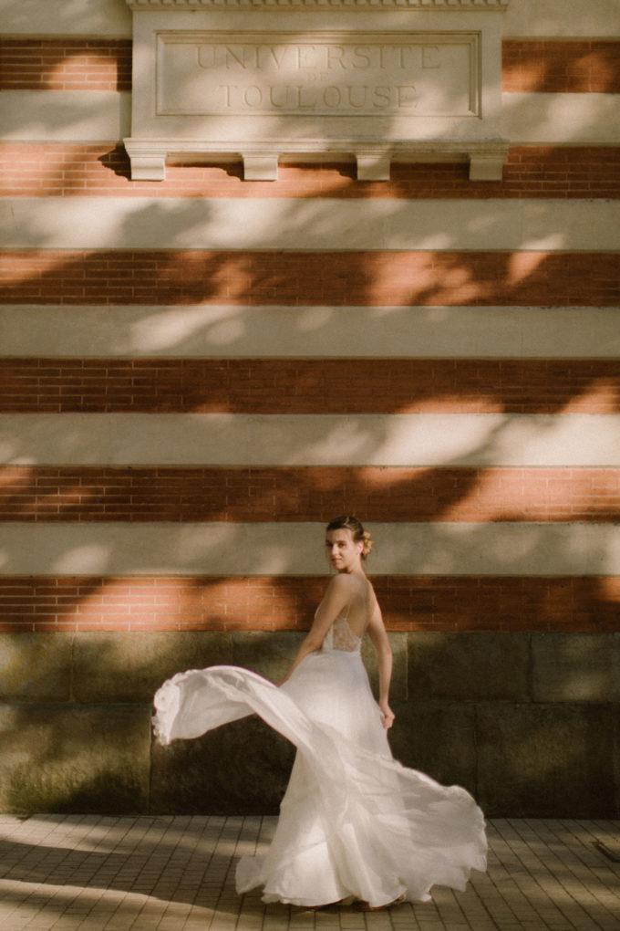 Plan large de la robe Laura en mouvement devant l'Université de Toulouse