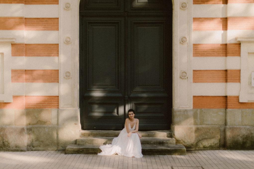 Plan d'ensemble de la robe Laura portée par une femme assise sur des marches devant une porte d'entrée