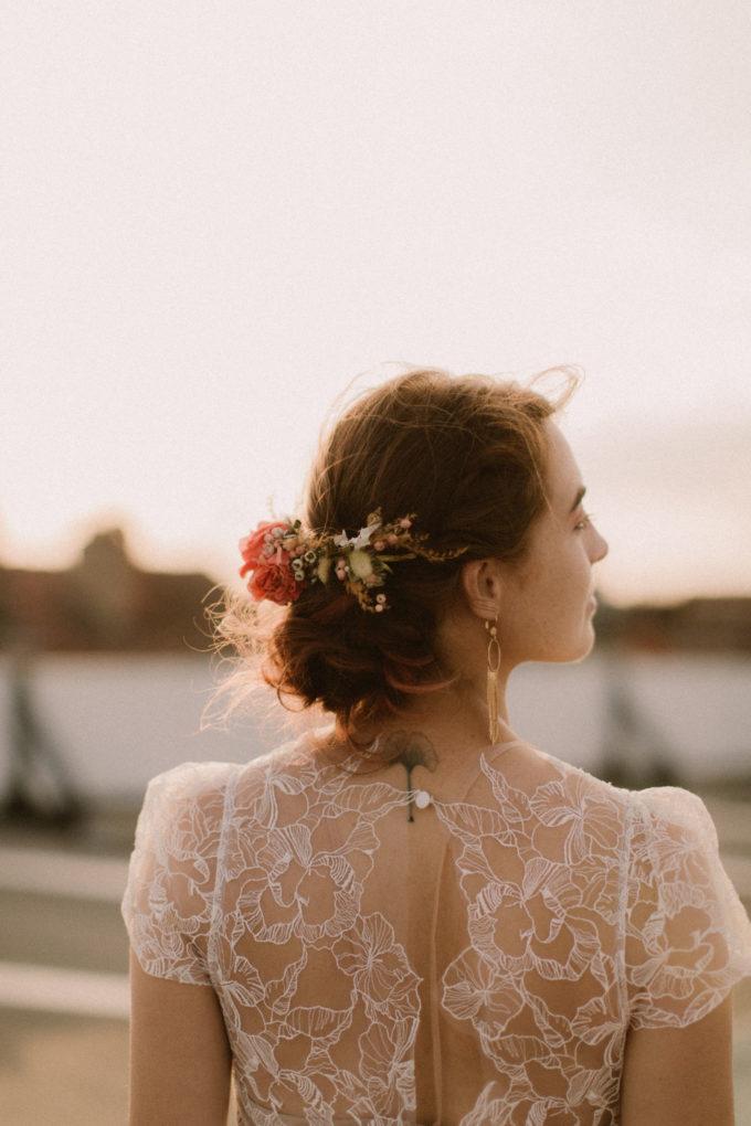 Plan poitrine de dos de la robe Naïs, fleurs de La Baraque à Fleurs dans les cheveux et boucles d'oreilles La Pépite by Pujol