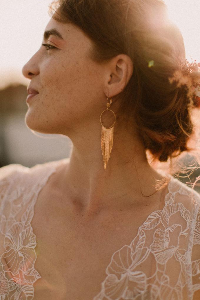 Photo des boucles d'oreilles LaPépitebyPujol et du haut du décolleté de la robe Naïs